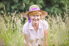 Positivity. Happy Senior Peasant Woman in Meadow smiling. Mature Friendly Lady in Bonnet Stock Images