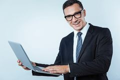 Smart man with laptop beaming into camera Royalty Free Stock Photo