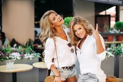 Positivity and pretty girls posing outdoor near cafe and showing peace. Positivity and pretty girls wearing similar in jeans shorts and white shirts, posing stock photography