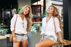 Positivity and pretty girls posing outdoor near cafe and showing peace. Positivity and pretty girls wearing similar in jeans shorts and white shirts, posing stock images