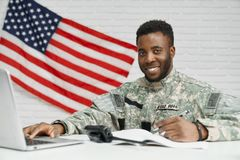 Positivity soldier of American army writing documents. Positivity soldier and worker of American army writing documents, using laptop and smiling at camera royalty free stock photos
