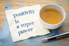 Positivity is a super power. Inspiraitonal handwriting on a napkin with a cup of tea Stock Photos