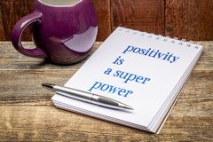 Positivity is a super power. Text in a sketchbook with a mug of hot tea or coffee stock image