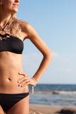 Positivity. Torso of a beautiful young woman wearing black swimsuit on a beach Royalty Free Stock Photography
