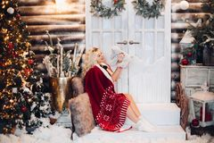 Positivity woman siitng on stairs wearing in plaid embracing teddy bear. Positivity blonde woman siitng on stairs against door, wearing in red plaid, holding royalty free stock photo