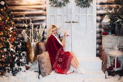 Positivity woman siitng on stairs wearing in plaid embracing teddy bear. Positivity blonde woman siitng on stairs against door, wearing in red plaid, holding royalty free stock photography