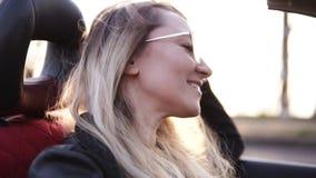 Positivo, sonriendo, muchacha de pelo largo en las gafas de sol transparentes que conducen su coche del cabriolé en la ciudad Muj almacen de video