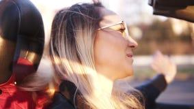 Positivo, sonriendo, muchacha de pelo largo en las gafas de sol transparentes que conducen su coche del cabriolé en la ciudad Muj almacen de metraje de vídeo