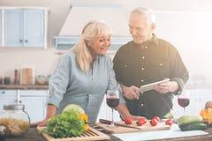 Positivt äldre gift par som avgör vad för att laga mat royaltyfri fotografi
