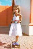 Positivt barn för stående på sparkcykeln Arkivfoto