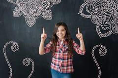 Positivt barn som ler och pekar till bilderna på väggen royaltyfri bild