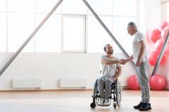 Positivt möte för fysisk terapeut med den rörelsehindrade patienten i idrottshallen arkivbild
