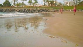 Posito Blanco, Spagna - circa novembre 2017: vista di acqua durante il rigonfiamento sulla spiaggia con la gente che riposa là stock footage