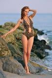 Posizione di modello abbastanza alla spiaggia rocciosa in costume da bagno Immagine Stock Libera da Diritti