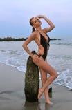 Posizione di modello abbastanza alla spiaggia rocciosa in costume da bagno Fotografia Stock