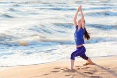 Posizione di pratica del guerriero di yoga della donna sulla spiaggia Fotografia Stock Libera da Diritti