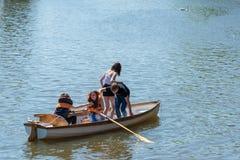 Posizioni di scambio della gente in una piccola barca per ottenere la maggior parte della squadra del efficienct immagine stock