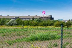Posnania shopping mall. The Posnania shopping mall building behind a field with grid fence on August 2017 in Poznan, Poland Stock Image