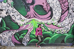 Posoes della ragazza davanti ad una grande opera d'arte dei graffiti, Pechino, Cina Fotografia Stock