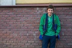 Pospolity młody człowiek jest ubranym zieloną koszulki kurtkę, cajgi przeciw czerwonemu ściana z cegieł patrzeje kamera i Zdjęcia Royalty Free