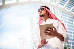 Posse árabe considerável do homem de negócio a tabuleta digital e vista ao lado esquerdo Escritório exterior ereto árabe do homem imagens de stock royalty free