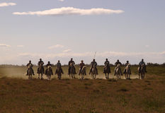Posse. Eleven silhouetted cowboys in straight line riding in dusty field Royalty Free Stock Image
