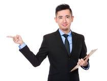 A posse asiática do homem de negócios com prancheta e o dedo apontam de lado Imagem de Stock Royalty Free