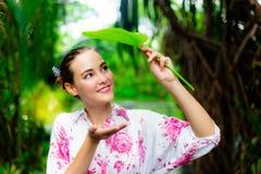 Posse bonita lindo da mulher uma folha para fechar sua cabeça quando chover dos it's fotos de stock