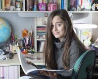 Posse da criança um livro estudando a menina com olhar curioso Imagens de Stock