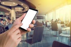 Posse da mão e smartphone humanos do toque com a tela vazia no fundo borrado da praça da alimentação fotografia de stock