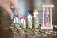 Posse da mão da mulher um modelo da casa posto sobre a moeda da pilha com crescimento no parque público, no dinheiro das economia imagens de stock