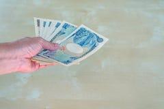 Posse da mão da mulher uma cédula japonesa dos ienes da moeda Foto de Stock Royalty Free