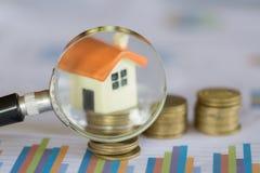 Posse da mão uma lupa que procura por uma casa nova, empréstimo para bens imobiliários ou para salvar no futuro o dinheiro para a imagem de stock