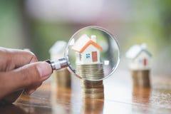 Posse da mão uma lupa que procura por uma casa nova, empréstimo para bens imobiliários ou para salvar no futuro o dinheiro para a fotografia de stock royalty free
