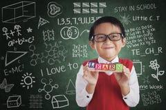 A posse de sorriso do menino aprende palavras cruzadas na classe Fotografia de Stock Royalty Free