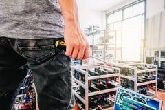 A posse do técnico a chave de fenda para reparar o muitos computador fotografia de stock