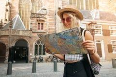 A posse e o olhar da menina do viajante traçam em Amsterdão Turista do moderno que procura a direção certa no mapa, aventura do c imagens de stock royalty free