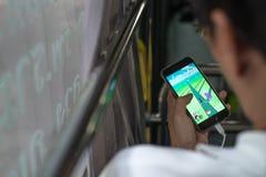 A posse não identificada do homem um telefone ao jogar Pokemon vai em sua mão na coletânea Fotos de Stock