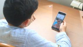 Posses do adolescente do menino um bate-papo video com uma mulher em um smartphone video estoque