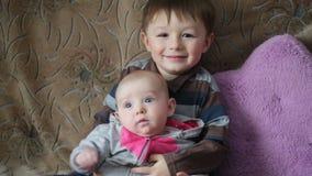Posses do rapaz pequeno nas mãos ela irmãs de sorriso video estoque