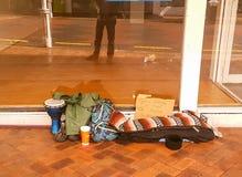 Possessões dos mendigos no passeio na frente da loja vaga com han Imagem de Stock Royalty Free