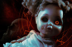 Possessed demonic doll. Possessed demonic horror doll with red pentacles, glowing eye & human skull on background Royalty Free Stock Images