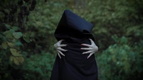 Possessed by demons woman is walking in a forest, holding her shoulders by hands with sharp vivid claws. Possessed by demons woman is wearing black hood, is stock video footage
