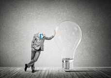 He possesses creative thinking. Headless businessman in empty room leaning on glass light bulb Stock Photos