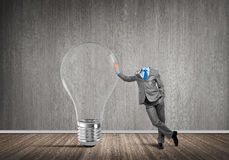 He possesses creative thinking. Headless businessman in empty room leaning on glass light bulb Royalty Free Stock Photos