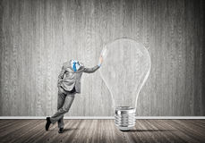 He possesses creative thinking. Headless businessman in empty room leaning on glass light bulb Stock Photo