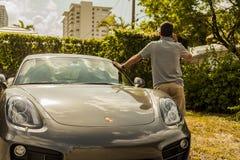 Possibilité éloignée d'un jeune homme au téléphone, maigre sur Porsche Cayman photo stock