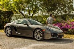Possibilité éloignée d'un jeune homme au téléphone, maigre sur Porsche Cayman image stock