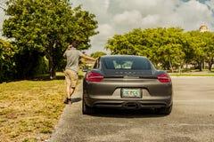 Possibilité éloignée d'un jeune homme au téléphone, maigre sur Porsche Cayman Image libre de droits