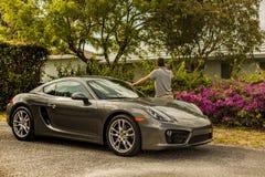 Possibilité éloignée d'un jeune homme au téléphone, maigre sur Porsche Cayman photographie stock